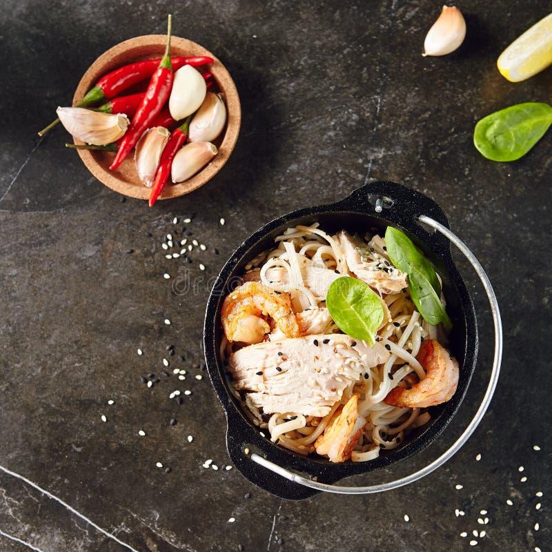 Νουντλς με τις γαρίδες, κοτόπουλο, στο σφαιριστή μετάλλων με τους σπόρους σουσαμιού στοκ φωτογραφία με δικαίωμα ελεύθερης χρήσης
