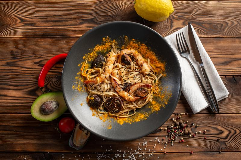 Νουντλς Σιγκαπούρη-ύφους με τα μανιτάρια shiitake και γαρίδες σε ένα μαύρο πιάτο σε ένα ξύλινο υπόβαθρο στοκ εικόνες