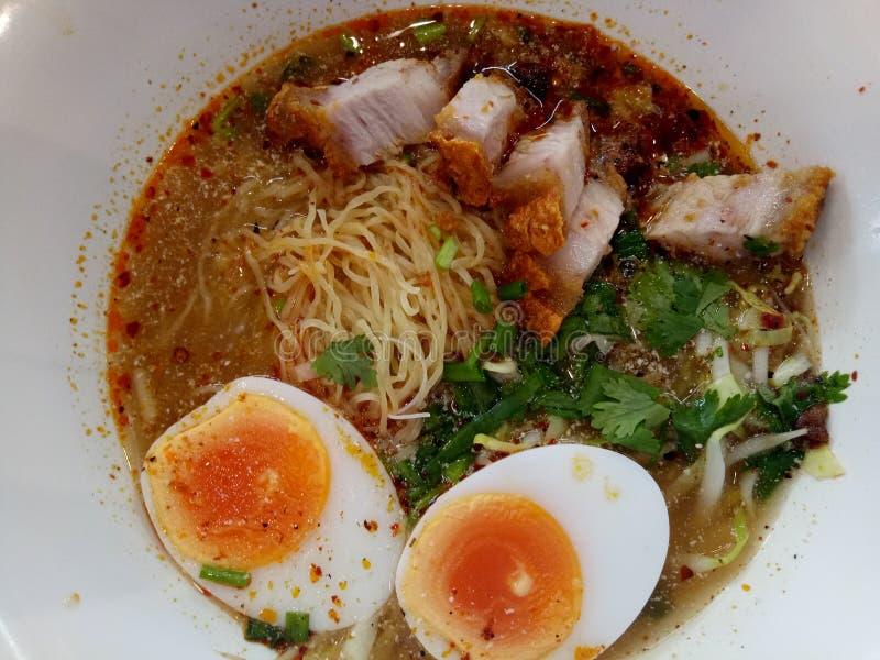 Νουντλς του Tom Yum με τα βρασμένα αυγά και το τριζάτο χοιρινό κρέας στοκ φωτογραφίες