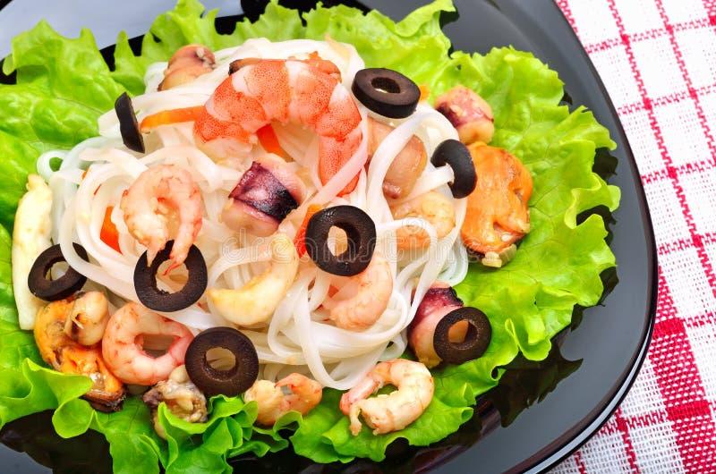 Νουντλς ρυζιού με τα θαλασσινά, ελιές, πράσινη σαλάτα στο μαύρο πιάτο στοκ εικόνες με δικαίωμα ελεύθερης χρήσης