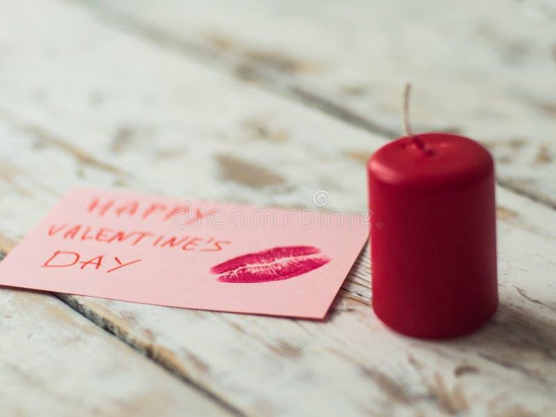 Ντεκόρ βαλεντίνων ` s του ST με το κόκκινο κερί και κάρτα στο ξύλινο υπόβαθρο στοκ φωτογραφία