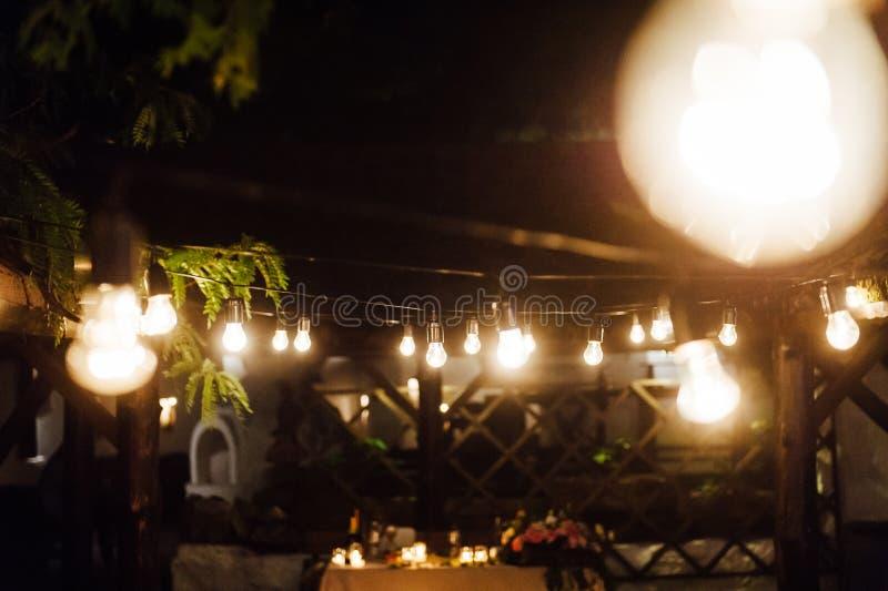 Ντεκόρ λαμπών φωτός στο υπαίθριο κόμμα γάμος στοκ εικόνες