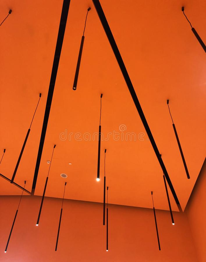 ντεκόρ με τους νέους ευθείς πολυελαίους και τους πορτοκαλιούς τοίχους στοκ εικόνα