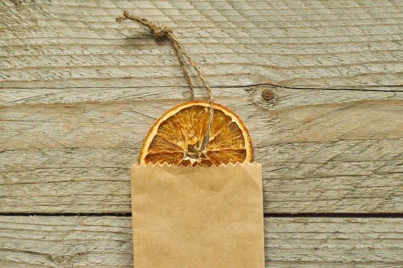 Ντεκόρ Χριστουγέννων Η ξηρά πορτοκαλιά φέτα στη συσκευασία εγγράφου τεχνών στο ξύλινο υπόβαθρο, τοπ άποψη, ελάχιστο επίπεδο βρέθη στοκ εικόνες