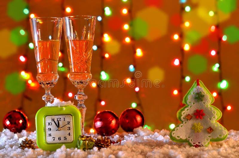 Ντεκόρ Χριστουγέννων με τα ποτήρια της σαμπάνιας και του ρολογιού στοκ φωτογραφία