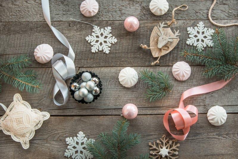 Ντεκόρ Χριστουγέννων που σχεδιάζεται σε μια ξύλινη επιφάνεια Το FIR διακλαδίζεται, ρόδινες/ασημένιες κορδέλλα και σφαίρα, άσπρο m στοκ φωτογραφίες με δικαίωμα ελεύθερης χρήσης