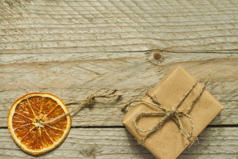 Ντεκόρ Χριστουγέννων Το ξηρό πορτοκαλί κιβώτιο φετών και δώρων στο έγγραφο τεχνών για το ξύλινο υπόβαθρο, τοπ άποψη, ελάχιστο επί στοκ εικόνες
