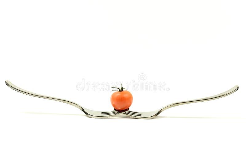 Ντομάτα στην ισορροπία σε δύο δίκρανα στοκ φωτογραφία