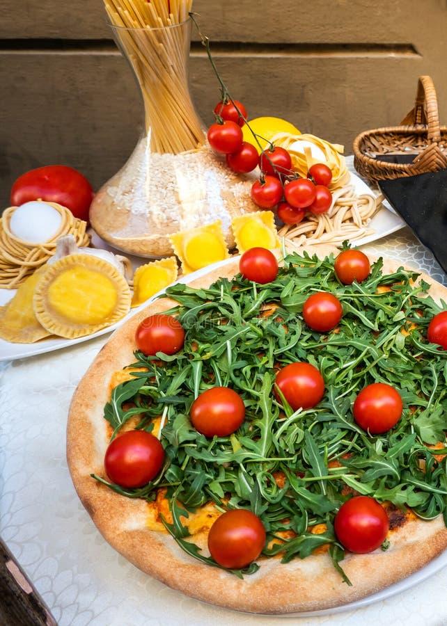 Ντομάτες ζυμαρικών πιτσών και φυτικά, χαρακτηριστικά ιταλικά τρόφιμα, που βλέπουν το ROM την κορυφή σε έναν πίνακα έξω από ένα εσ στοκ φωτογραφία με δικαίωμα ελεύθερης χρήσης