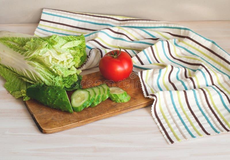 Ντομάτες και αγγούρια με το κινεζικό λάχανο στον πίνακα για την προετοιμασία της σαλάτας στοκ φωτογραφία