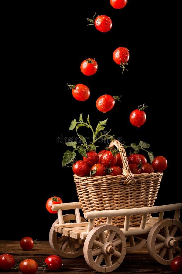 Ντομάτες κερασιών που περιέρχονται στο καλάθι Μετεωρισμός τροφίμων στοκ εικόνα με δικαίωμα ελεύθερης χρήσης