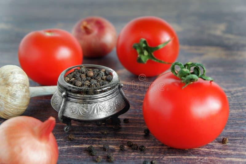 Ντομάτες, μαύρο πιπέρι, σκόρδο και κρεμμύδια στο ξύλινο υπόβαθρο Ακατέργαστα λαχανικά στοκ εικόνες