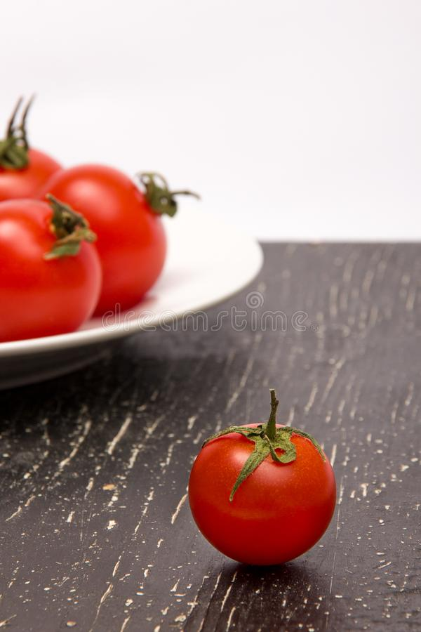 Ντομάτες στο πιάτο και μια στο μαύρο πίνακα στοκ φωτογραφία με δικαίωμα ελεύθερης χρήσης