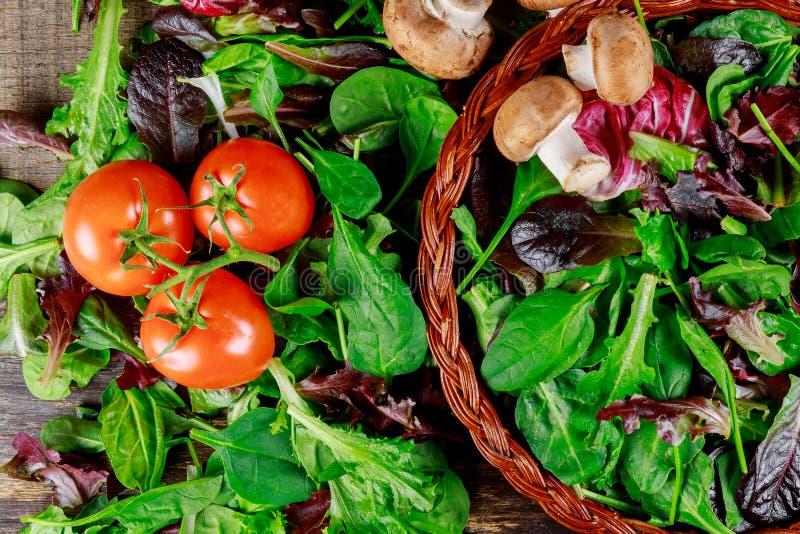 Ντομάτες, champignons και φύλλα σαλάτας γύρω από το παλαιό σκοτεινό υπόβαθρο, τοπ άποψη στοκ εικόνες
