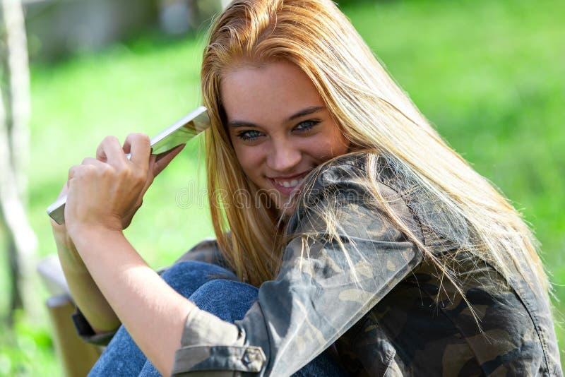 Ντροπαλή νέα γυναίκα διασκέδασης που χαμογελά στη κάμερα στοκ φωτογραφίες