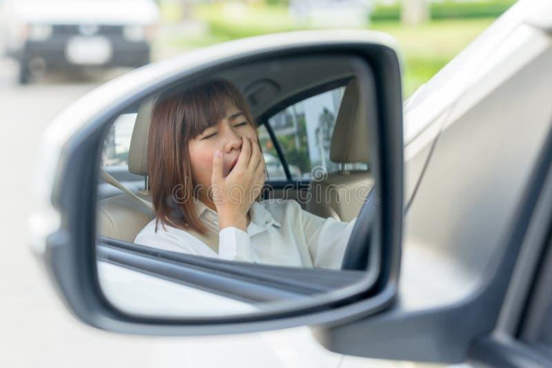 Νυσταλέα, κουρασμένη νέα γυναίκα πορτρέτου κινηματογραφήσεων σε πρώτο πλάνο που οδηγεί το αυτοκίνητό της κατόπιν στοκ φωτογραφίες