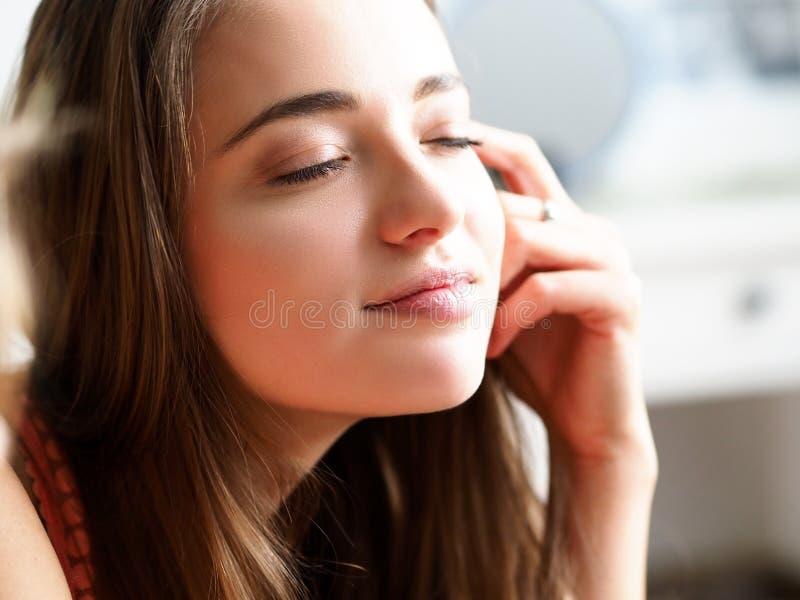 Νυσταλέα νέα όμορφη γυναίκα που απολαμβάνει τις ηλιαχτίδες μετά από τον ύπνο νύχτας στοκ φωτογραφία