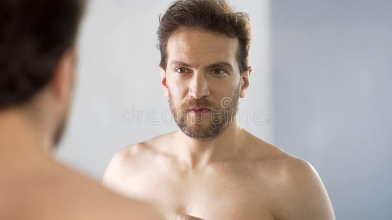 Νυσταλέο άτομο που εξετάζει στον καθρέφτη το λουτρό, έλλειψη ύπνου, που υφίσταται την αϋπνία στοκ εικόνες