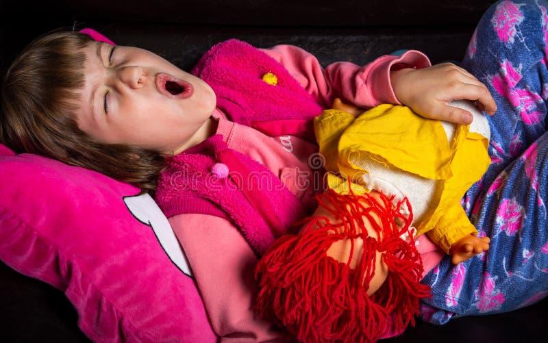 Νυσταλέο κορίτσι με το παιχνίδι της στον καναπέ στοκ εικόνες με δικαίωμα ελεύθερης χρήσης