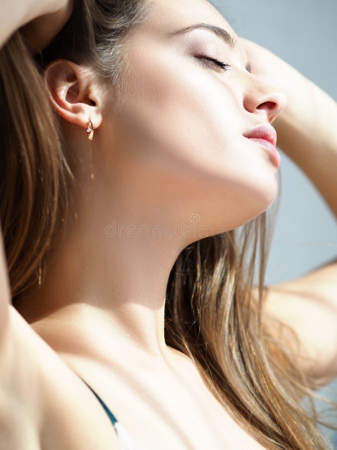 Νυσταλέο νέο όμορφο τέντωμα γυναικών μετά από τον ύπνο νύχτας στοκ εικόνα
