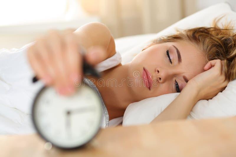 Νυσταλέα νέα γυναίκα που δοκιμάζει το ξυπνητήρι θανάτωσης στοκ φωτογραφία με δικαίωμα ελεύθερης χρήσης