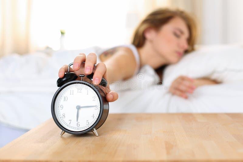 Νυσταλέα νέα γυναίκα που δοκιμάζει το ξυπνητήρι θανάτωσης στοκ εικόνες με δικαίωμα ελεύθερης χρήσης