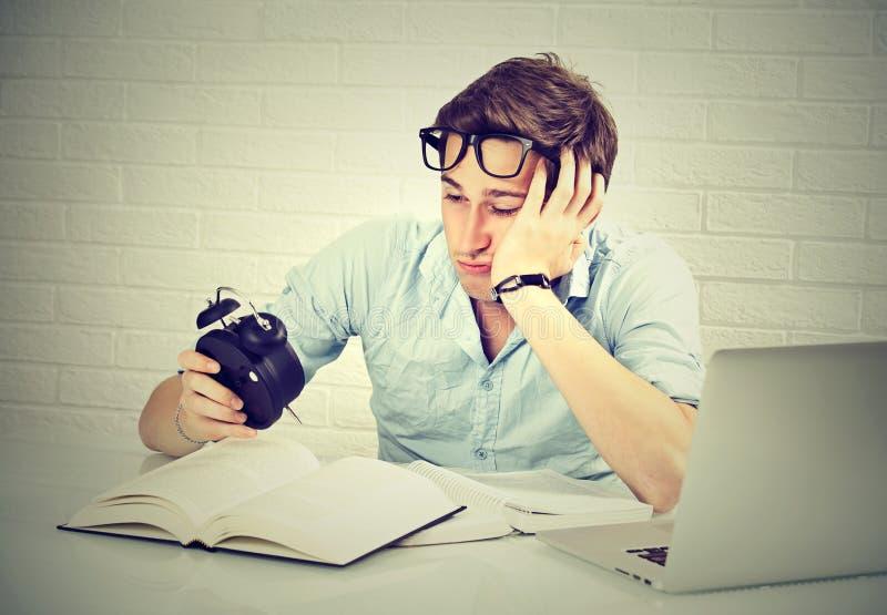 Νυσταλέο άτομο με το φορητό προσωπικό υπολογιστή βιβλίων που εξετάζει το ξυπνητήρι στοκ φωτογραφία με δικαίωμα ελεύθερης χρήσης