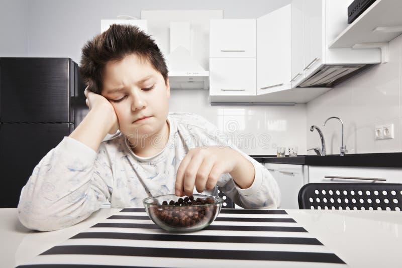 Νυσταλέο παιδί που τρώει την κινηματογράφηση σε πρώτο πλάνο δαγκωμάτων δημητριακών στοκ φωτογραφίες