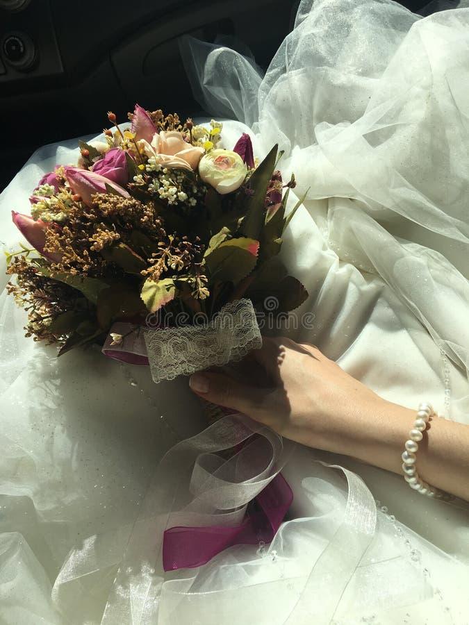 Νυφικά εσθήτα υποβάθρου νυφών και λουλουδιών και περιδέραιο μαργαριταριών στοκ εικόνες