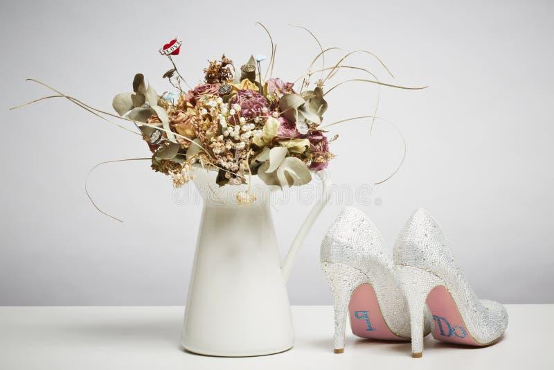 Νυφικά παπούτσια και ξηρά λουλούδια στο βάζο στοκ εικόνες με δικαίωμα ελεύθερης χρήσης