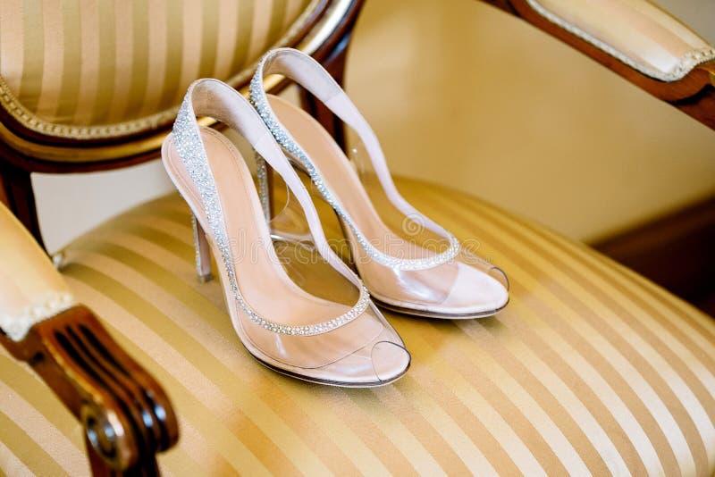 Νυφικά παπούτσια σε μια καρέκλα με μια χρυσή ταπετσαρία και ξύλινες λαβές στοκ εικόνα με δικαίωμα ελεύθερης χρήσης