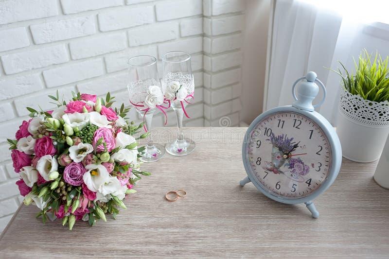 νυφική ανθοδέσμη με τα γαμήλια δαχτυλίδια και τα γυαλιά κρασιού στον πίνακα το πρωί της ημέρας, όμορφα εκλεκτής ποιότητας ρολόγια στοκ εικόνα