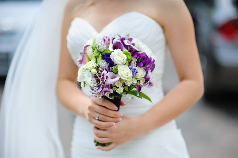 Νυφική ανθοδέσμη των πορφυρών και άσπρων λουλουδιών στα χέρια της νύφης στοκ φωτογραφίες με δικαίωμα ελεύθερης χρήσης