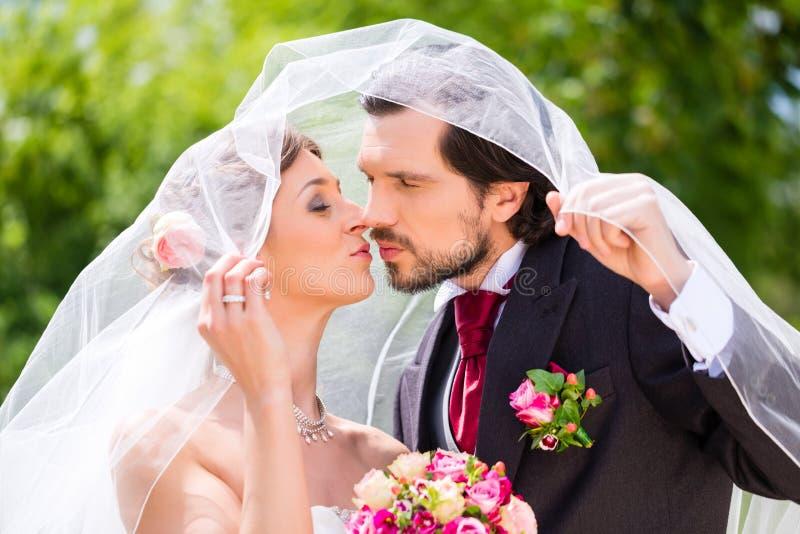 Νυφικό φίλημα ζευγαριού κάτω από το πέπλο στο γάμο στοκ φωτογραφία
