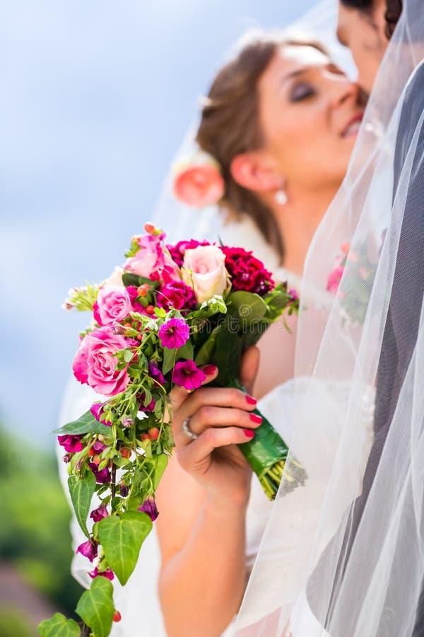 Νυφικό φίλημα ζευγαριού κάτω από το πέπλο στο γάμο στοκ εικόνες
