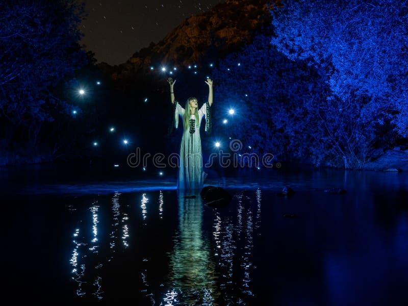 Νυχτερινή φωτογραφία, φωτισμός, που αναπαριστά ένα μοντέλο στο ποτάμι με σκιές φτιαγμένες από φανάρια στο ποτάμι στοκ φωτογραφία