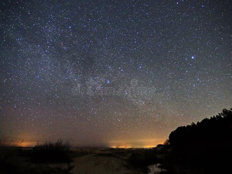 Νυχτερινός ουρανός και γαλακτώδη αστέρια τρόπων, αστερισμός αστερισμού του Κύκνου πέρα από τη θάλασσα στοκ εικόνες