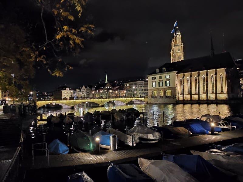 Νυχτερινό τοπίο Ζυρίχης Ελβετίας με σκάφη και καθεδρικό ναό Grossmunster σε απόσταση στοκ εικόνες