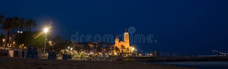 Νωρίς το πρωί θέα των ακτών της παραλίας στην πόλη Sitges κοντά στη Βαρκελώνη στην Καταλονία της Ισπανίας με το φωτισμένο Parroqu στοκ εικόνες