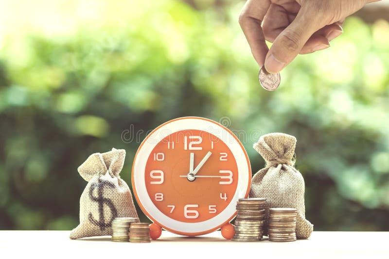 Νόμισμα εκμετάλλευσης χεριών πέρα από moneybags και πορτοκαλί ρολόι στο ξύλινο tabl στοκ εικόνα