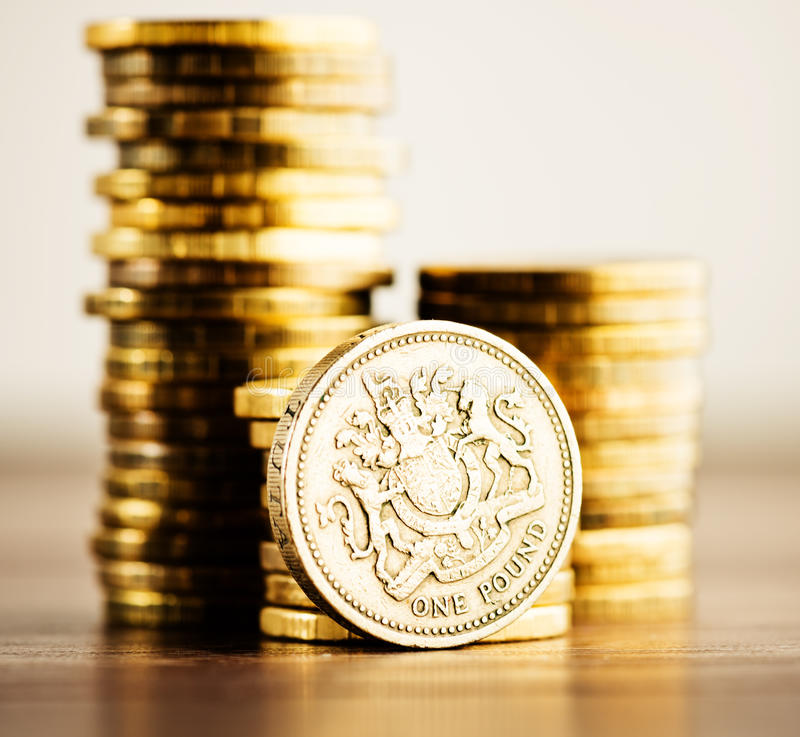 Νόμισμα GBP λιβρών και χρυσά χρήματα στο γραφείο στοκ φωτογραφία