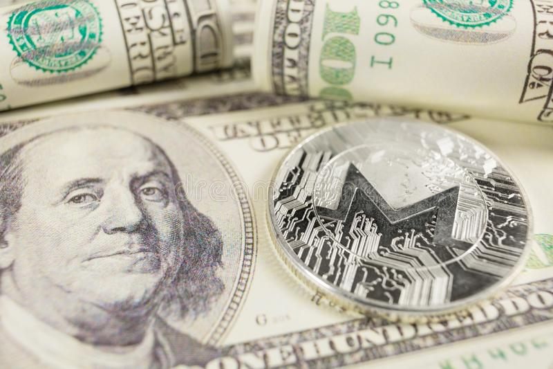 Νόμισμα MONERO στο υπόβαθρο των λογαριασμών δολαρίων στοκ φωτογραφίες
