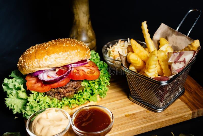 Νόστιμα αμερικανικά τρόφιμα - burger βόειου κρέατος με το ψημένα στη σχάρα κρέας και mayo εξυπηρέτησε με τα τηγανητά, coleslaw κα στοκ φωτογραφία με δικαίωμα ελεύθερης χρήσης