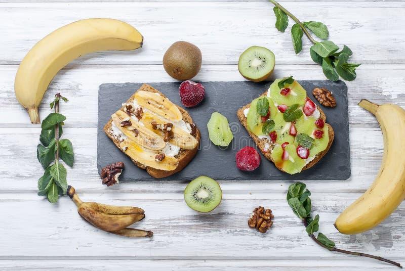 Νόστιμα γλυκά σάντουιτς με τις μπανάνες, τα καρύδια και τη σοκολάτα, ακτινίδιο, s στοκ εικόνες με δικαίωμα ελεύθερης χρήσης