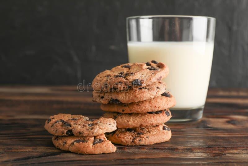 Νόστιμα μπισκότα τσιπ σοκολάτας και ποτήρι του γάλακτος στον ξύλινο πίνακα στοκ εικόνες