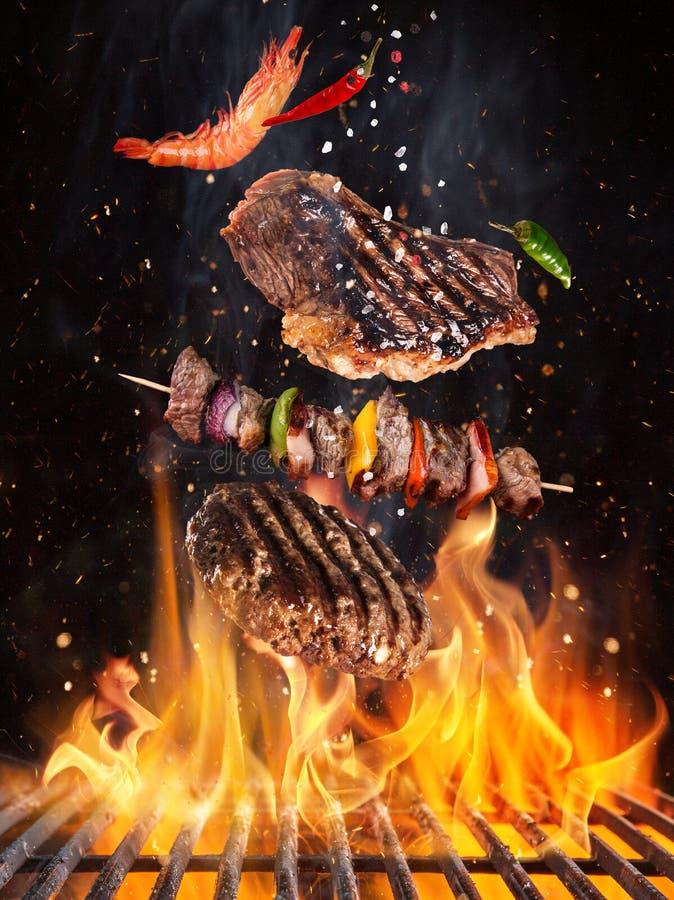 Νόστιμα μπριζόλες και οβελίδια βόειου κρέατος που πετούν επάνω από τη σχάρα χυτοσιδήρου με τις φλόγες πυρκαγιάς στοκ εικόνες με δικαίωμα ελεύθερης χρήσης