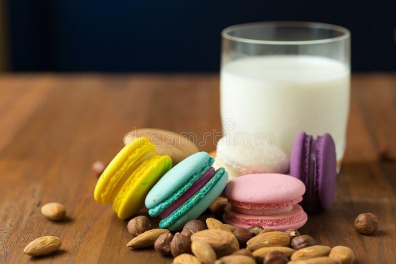 Νόστιμα macaroons και φλυτζάνι του γάλακτος με το αμύγδαλο στο ξύλινο υπόβαθρο στοκ φωτογραφία με δικαίωμα ελεύθερης χρήσης