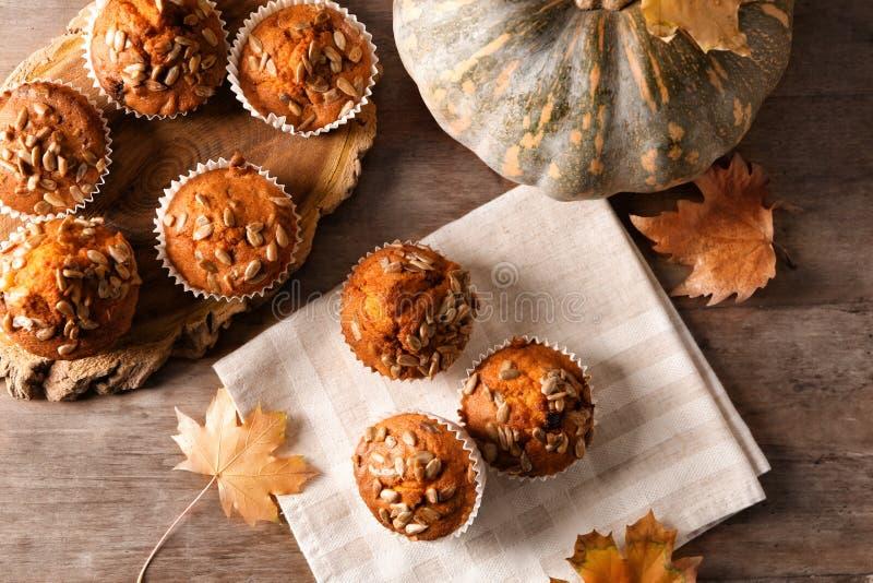 Νόστιμα muffins κολοκύθας με τους σπόρους ηλίανθων στον ξύλινο πίνακα στοκ εικόνες