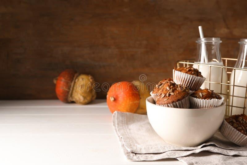 Νόστιμα muffins κολοκύθας με τους σπόρους ηλίανθων στο κύπελλο στον άσπρο πίνακα στοκ εικόνα με δικαίωμα ελεύθερης χρήσης