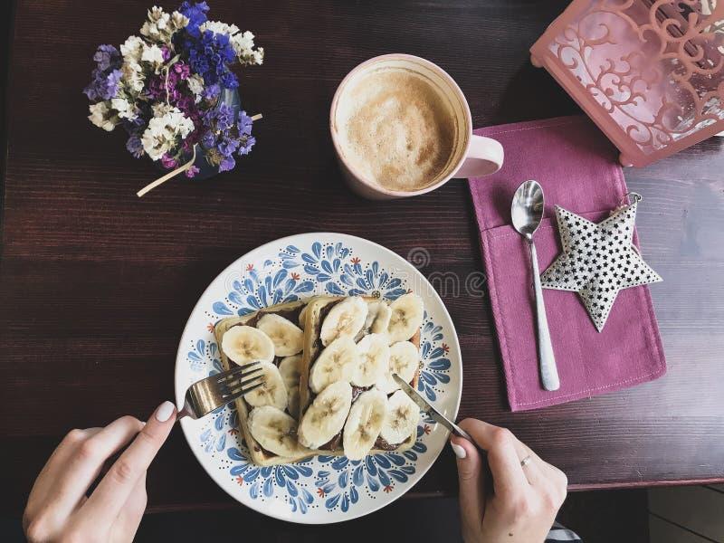 Νόστιμες βάφλες με τις μπανάνες και τη λειωμένη σοκολάτα, χέρια στοκ φωτογραφίες